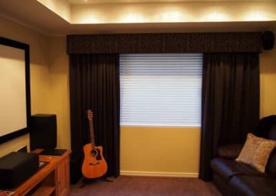 Home theatre with dark curtains and venetian blinds