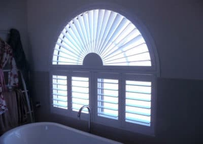 arched window shutters in bathroom