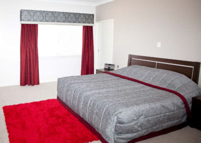 bedroom with red curtains and damask pelmet