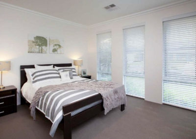 bedroom with three windows and venetian blinds