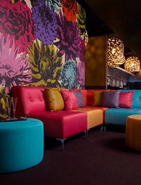 bright floral wallpaper with colourful couch interior