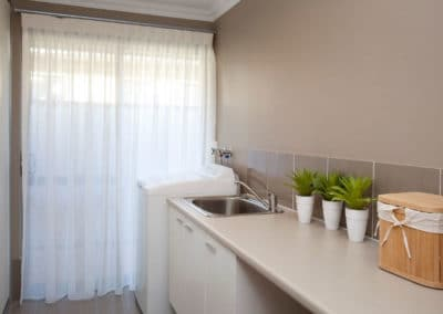 laundry room with white sheer curtains