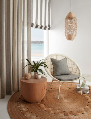 living room area with rattan rug and sheer striped curtains